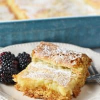 slice of gooey butter cake with blackberries on an ivory plate with fork