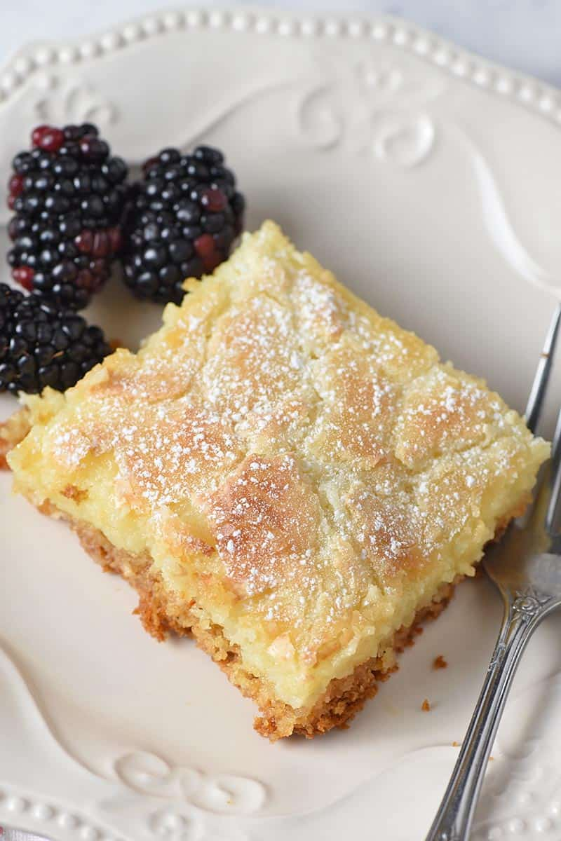 slice of gooey butter cake on ivory plate with blackberries