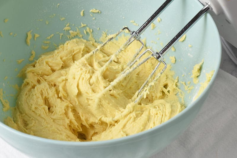 mixing ingredients for cake mix gooey butter cake crust in blue mixing bowl with hand mixer
