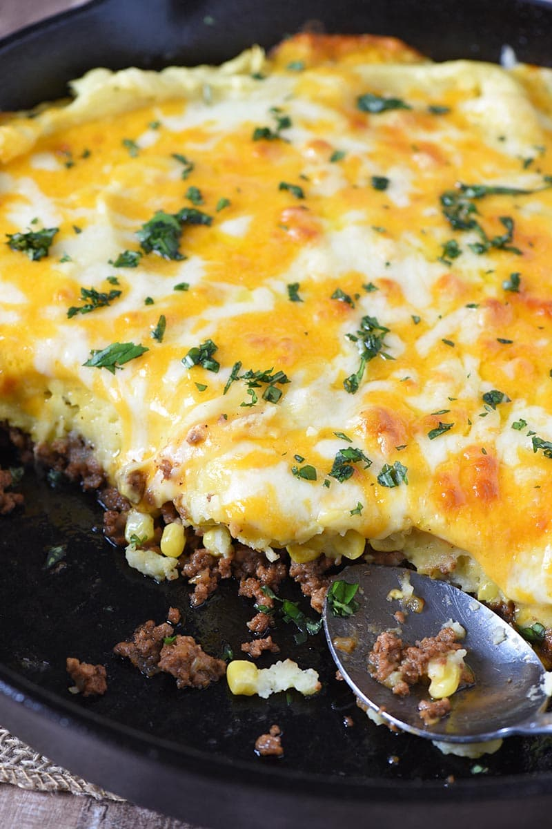 sloppy joe shepherd's pie in a cast iron skillet with a large spoon