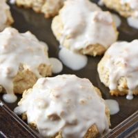 frosted cinnamon biscuits on baking sheet