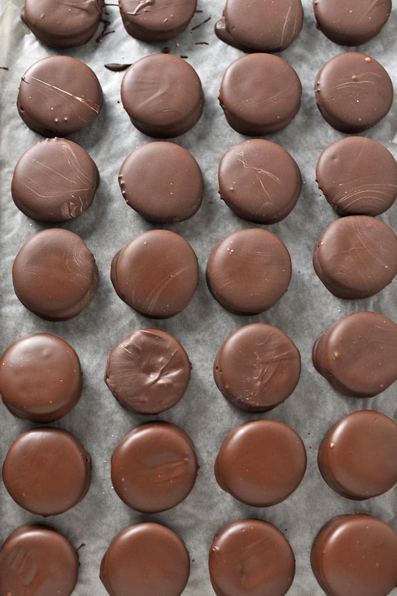 chocolate covered peanut butter crackers on wax paper covered baking sheet
