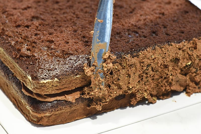 spreading chocolate buttercream dirt frosting on chocolate Minecraft cake with table knife