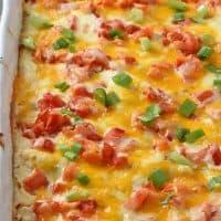creamy chicken enchiladas with sour cream sauce in white baking dish