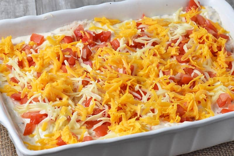 add shredded cheese to top of creamy chicken enchiladas in white baking dish