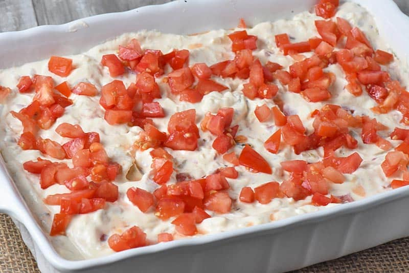 add tomatoes to top of chicken enchiladas in white baking dish