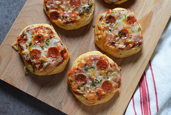 Grands Mini Supreme Pizzas are a quick and easy dinner or lunch recipe with Grands Biscuits, pizza sauce, veggies, cheese, and pepperoni.