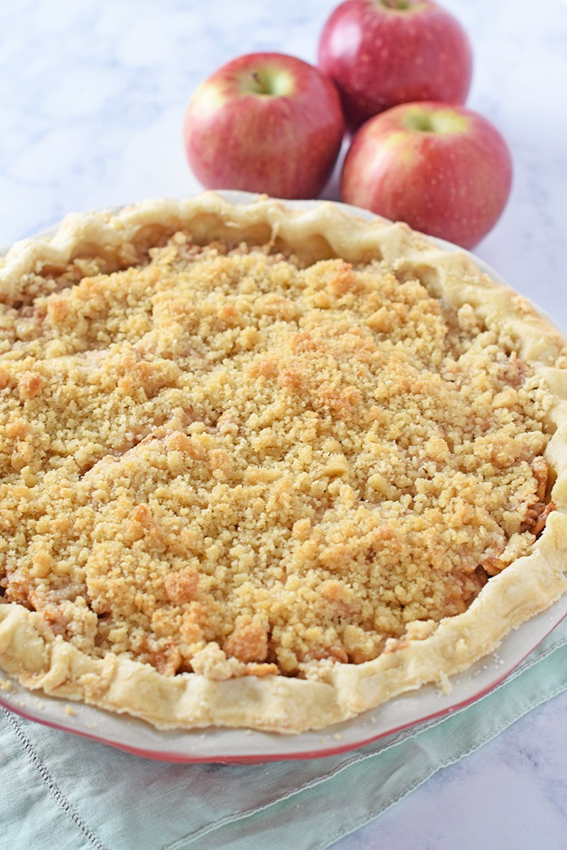whole apple crumb pie in ceramic pie plate
