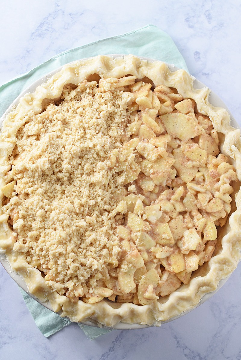 Dutch apple pie with half the Dutch apple pie topping on top and apple pie filling on one side