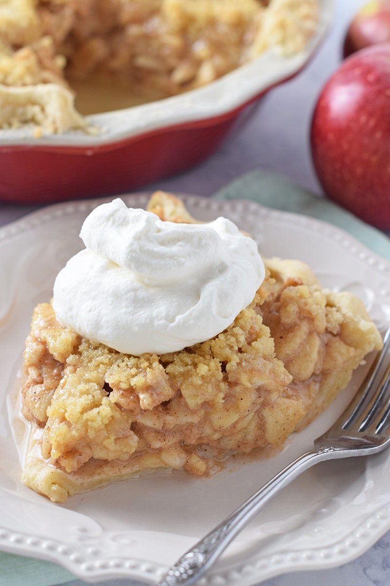 up close slice of the best apple pie recipe with whipped cream on top