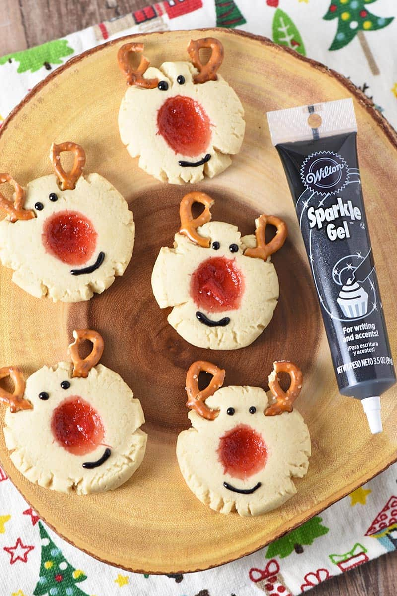 decorating reindeer thumbprint cookies with Wilton Sparkle Gel, adding eyes and mouth