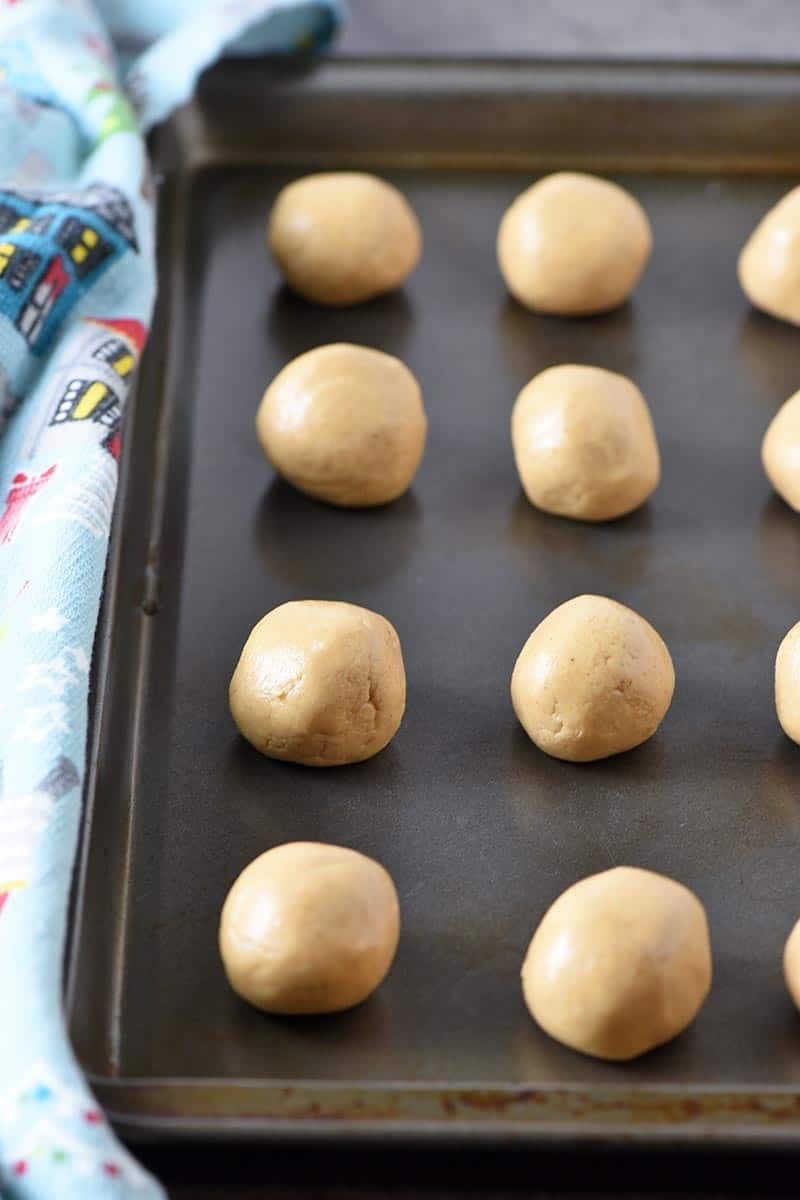 no bake peanut butter balls sitting on cookie sheet