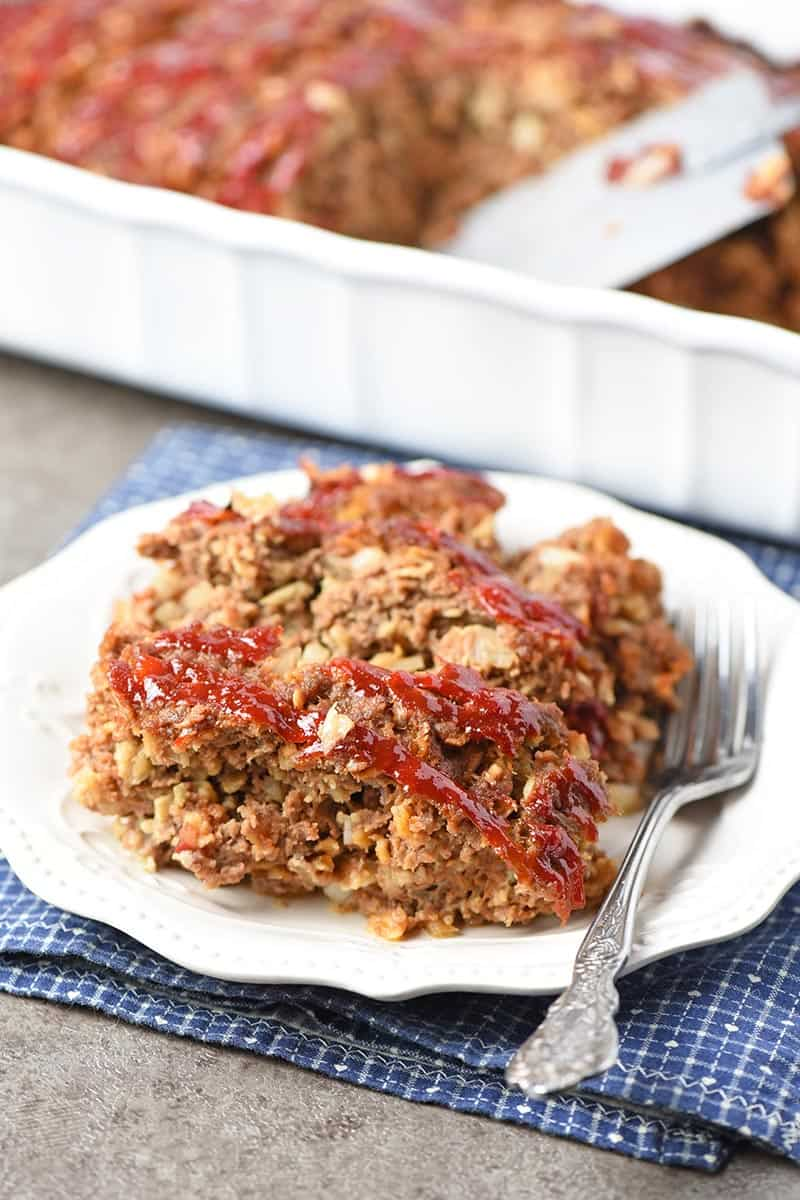 easy meatloaf recipe sliced on a pretty white plate ready to serve with a fork