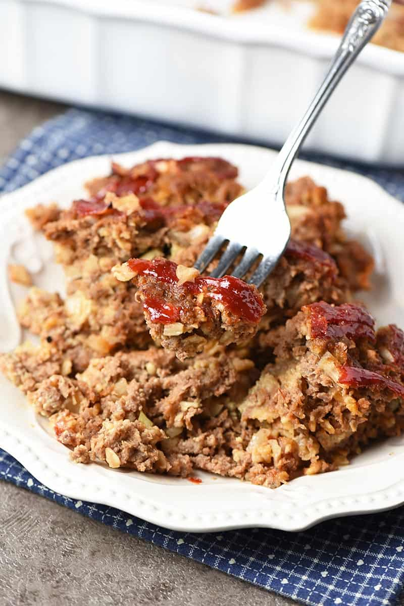 forked bite of meatloaf with oatmeal on white plate