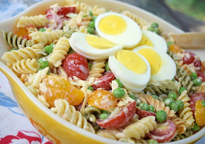 Rotini pasta coated with a lightly creamy dressing, mixed with fresh cucumbers, tomatoes, smoked cheese, and other delicious ingredients. Easy 30 minute pasta salad recipe!