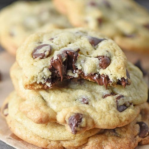 soft chocolate chip cookies stacked with melted chocolate chips and bite taken out of cookie
