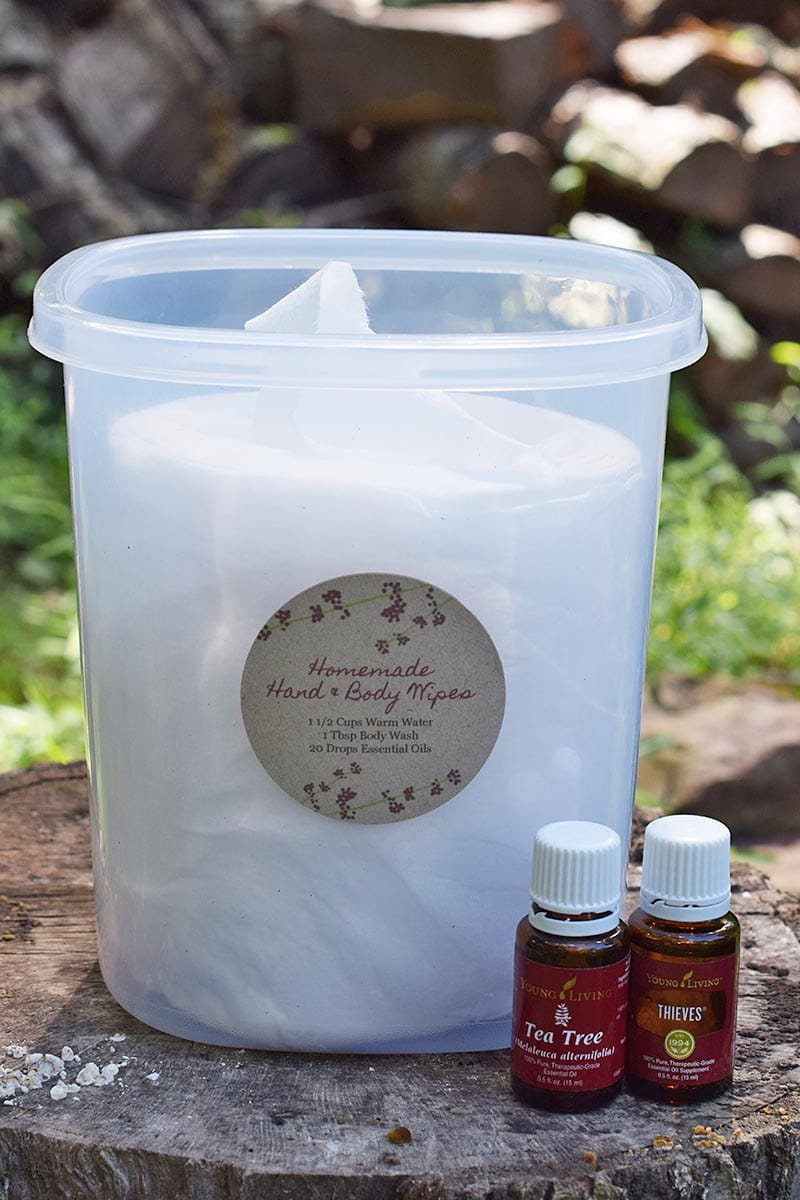 homemade camping wipes in plastic storage container with Young Living Tea Tree Oil and Thieves Oil