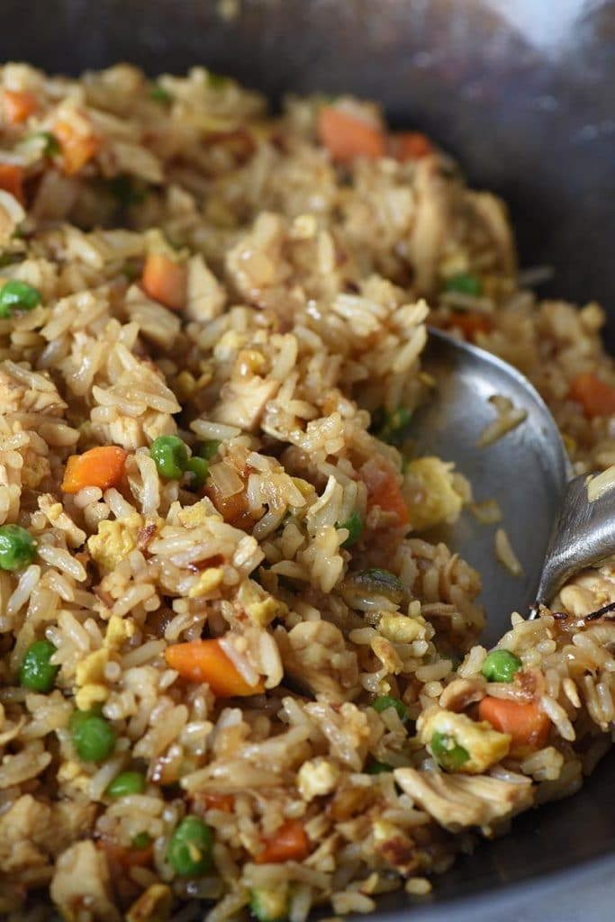 stir frying chicken fried rice with a metal spatula in a large wok