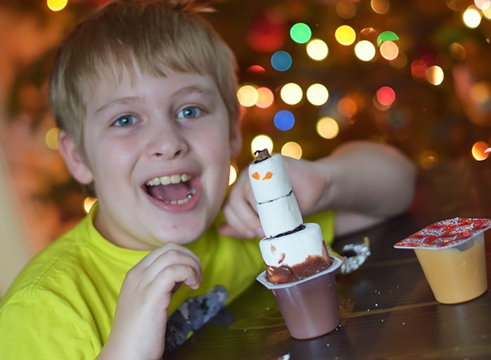 Kids bored on a cold winter day? Make an edible kids craft or kids snack with them. How to build a snowman in a pudding cup!