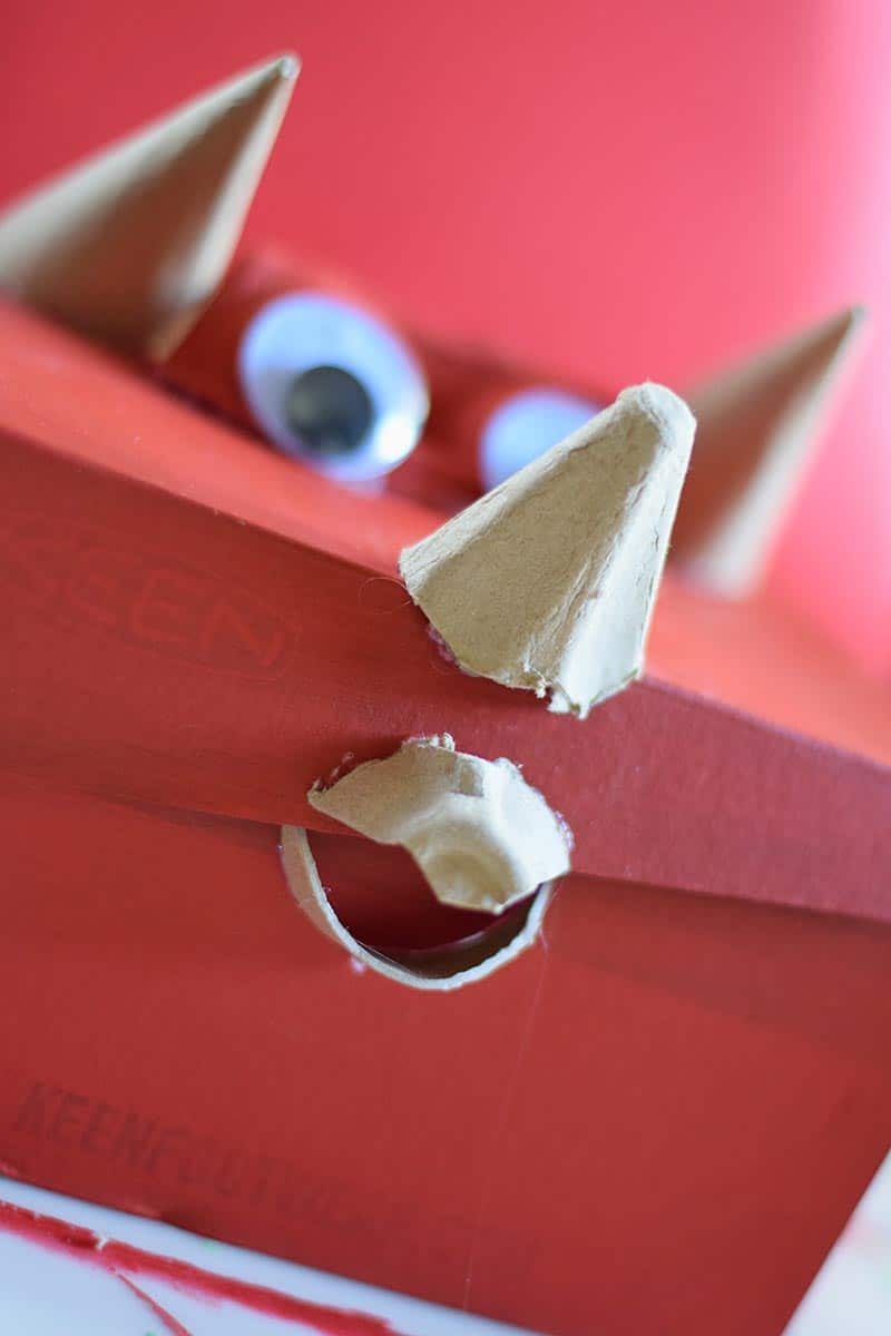 putting a Triceratops beak in place with pieces of an egg carton on a red Valentine box
