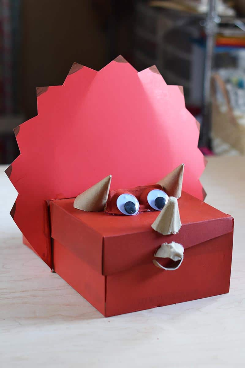 Triceratops dinosaur Valentine box painted red with eyes and horns, sitting on a wooden table