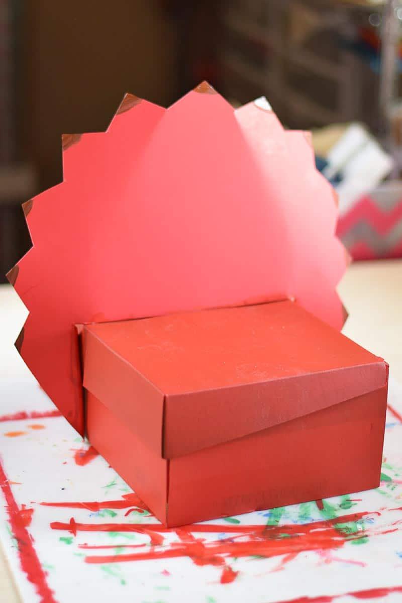 placing triceratops crest  onto shoebox to make a homemade Valentine box