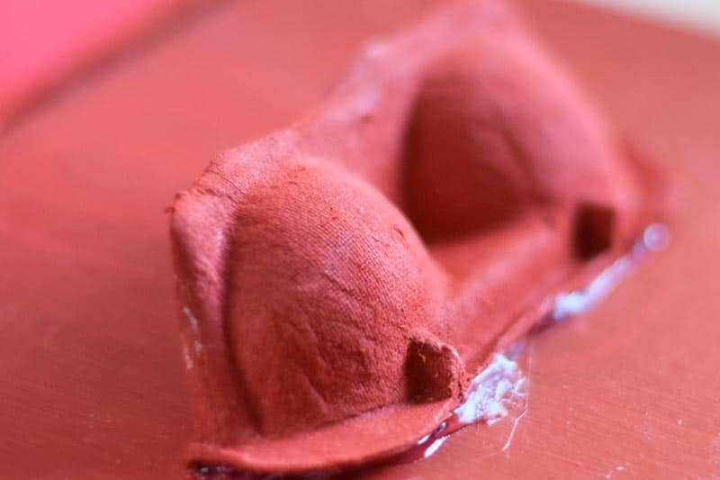 part of an egg carton painted red and glued onto a red painted shoebox