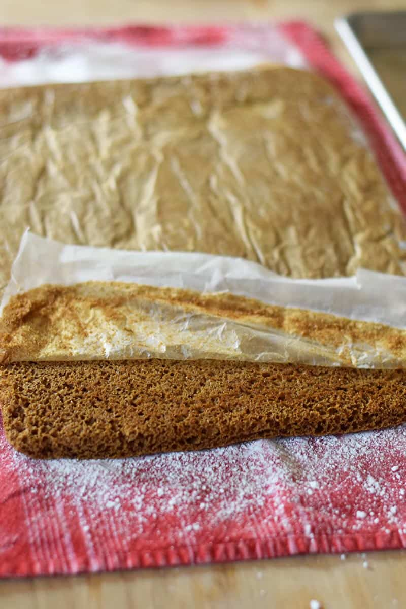 place the pumpkin roll cake onto a powdered sugar flour sack towel and peel off the wax paper