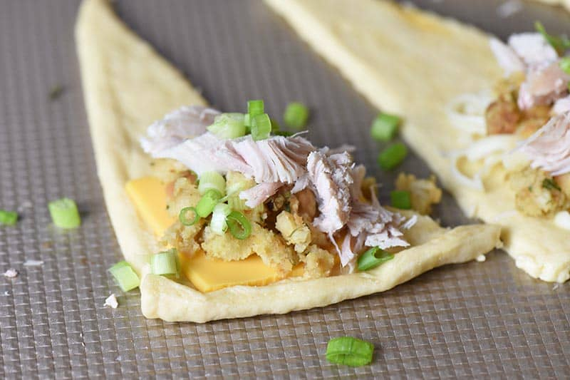 leftover turkey, stuffing, American cheese, and green onions being stuffed into a crescent roll for Thanksgiving appetizers