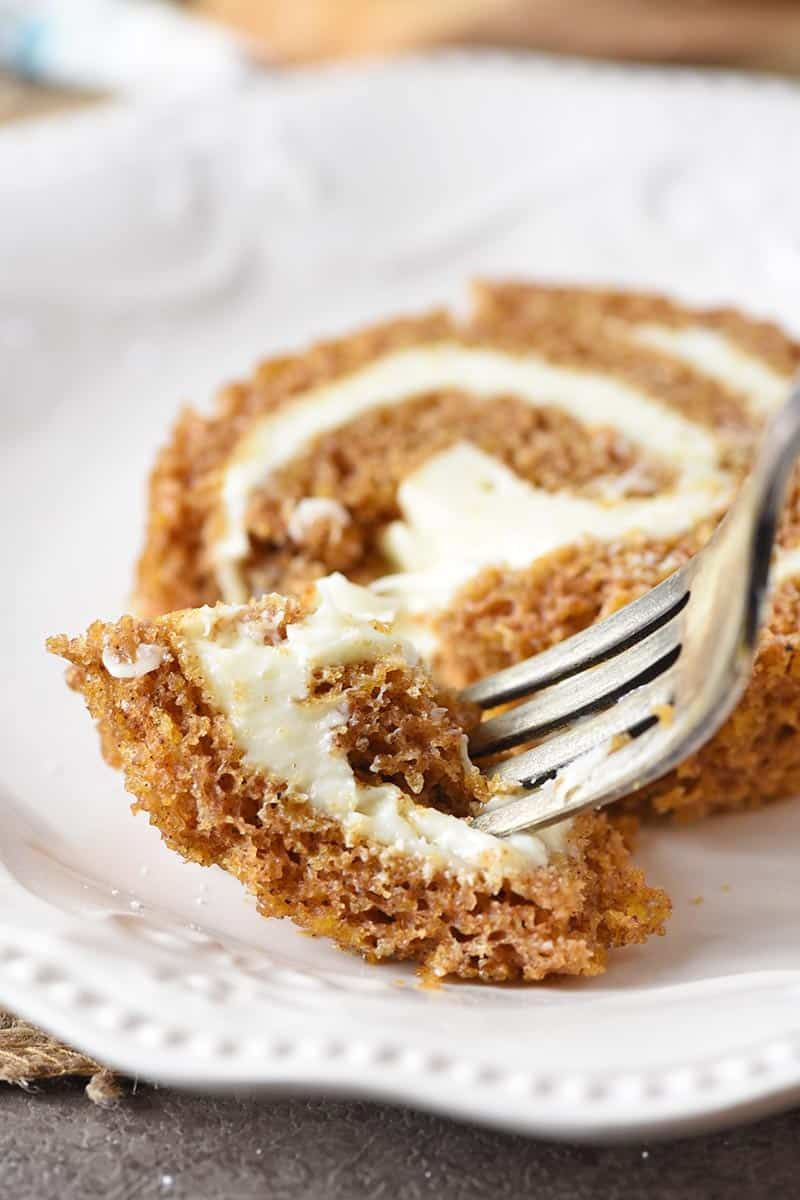 bite of pumpkin roll on a fork with ivory plate