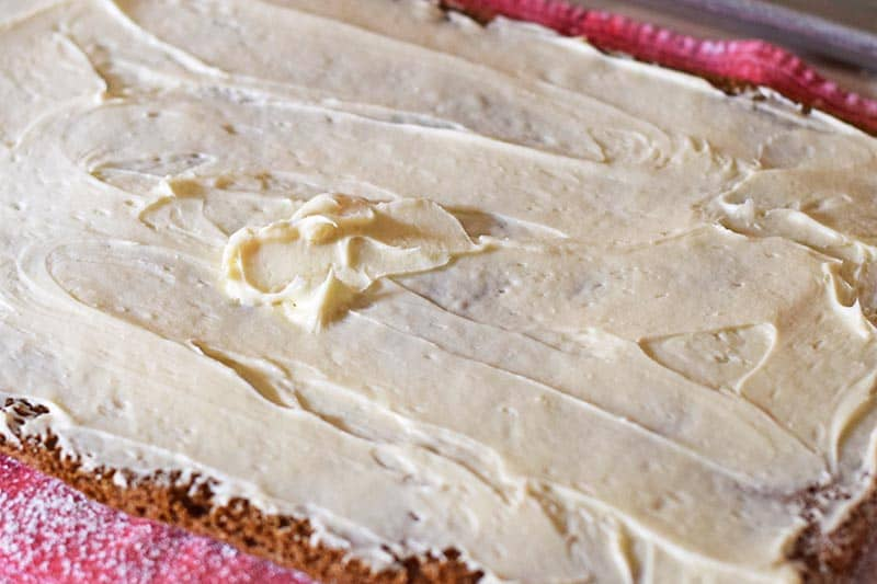 spread cream cheese filling onto pumpkin roll cake before rolling