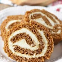 scrumptious pumpkin roll with a cream cheese filling, sliced on an ivory plate