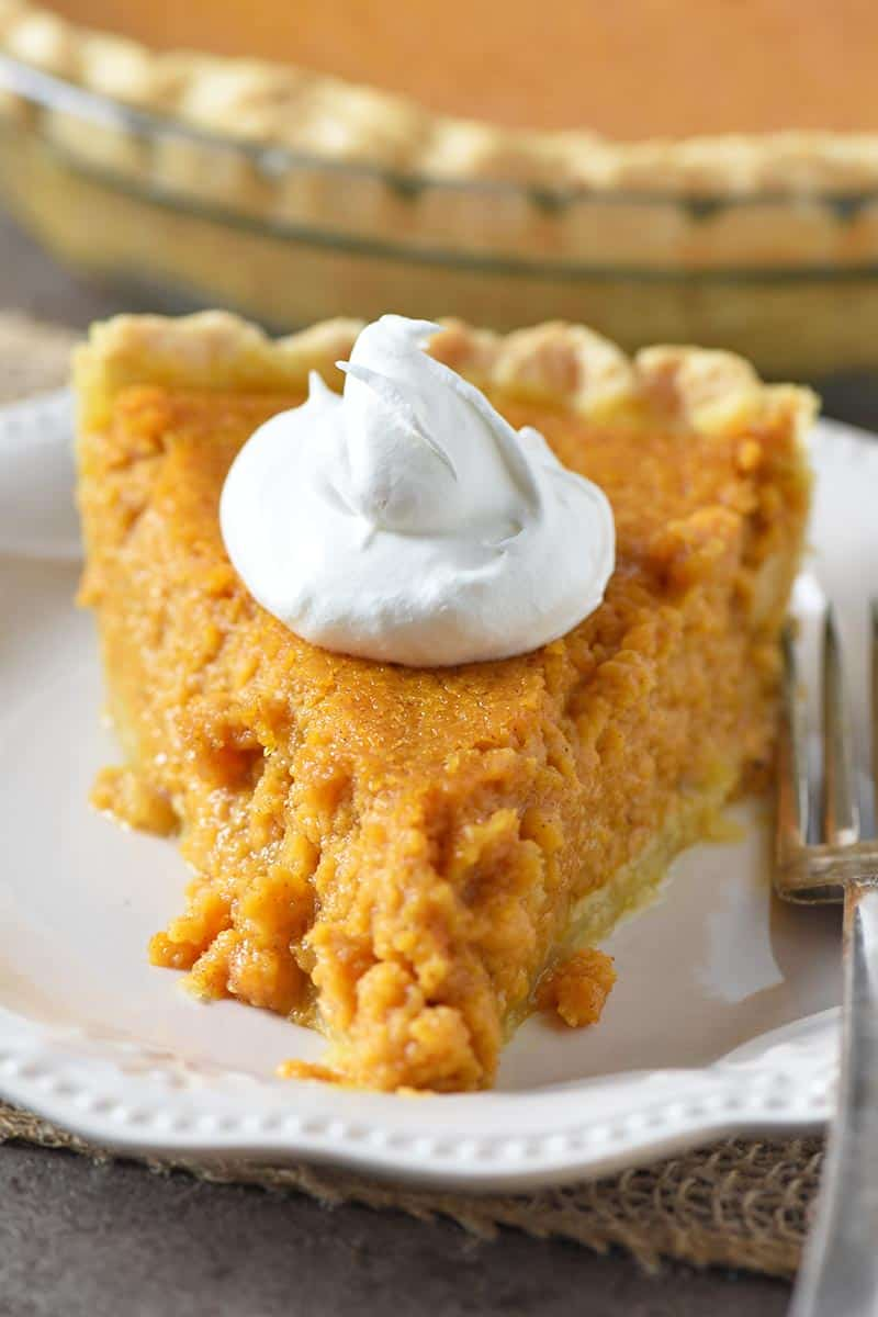 slice of southern sweet potato pie with whipped cream topping and fork on ivory colored plate