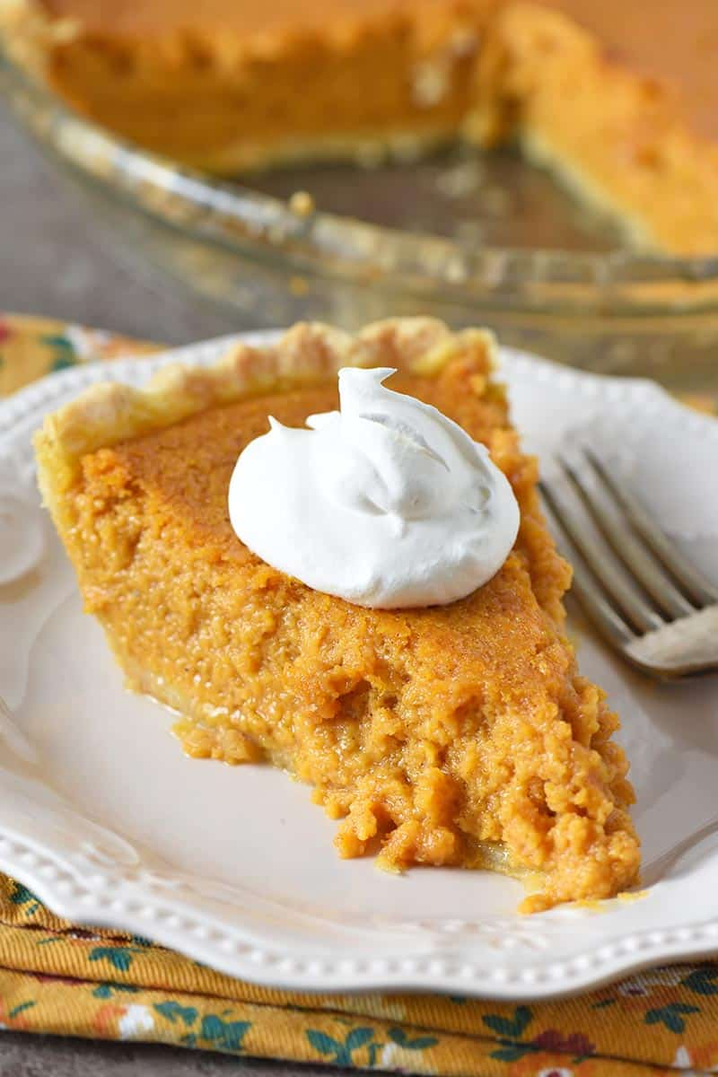 slice of sweet potato custard pie with whipped cream on white plate with fork
