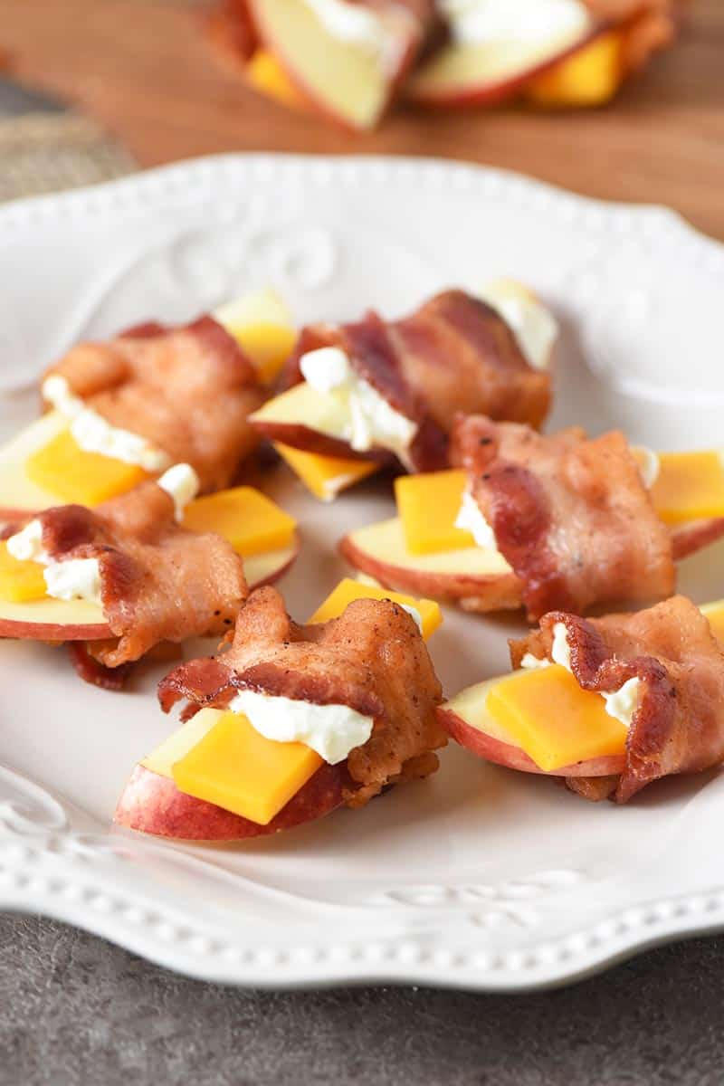 Bacon wrapped apples and cheese appetizers on a white plate