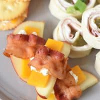 easy bacon appetizers, pinwheels, and cheese and crackers on a gray plate
