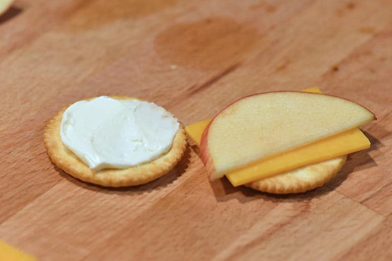 making apples and cheese crackers with cream cheese on wooden cutting board