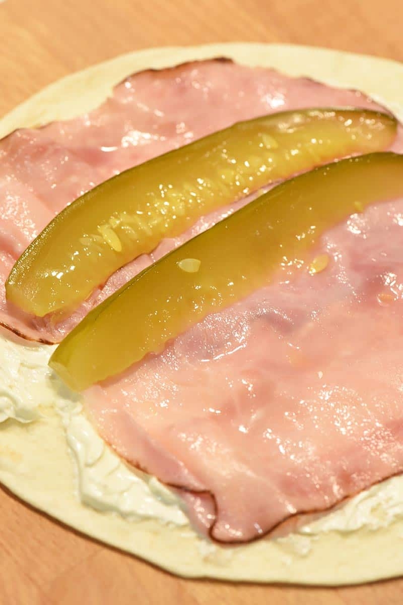 making pinwheels with cream cheese, ham, and dill pickles in a tortilla