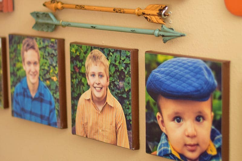 DIY canvas prints with family photos on gallery wall with metal arrows