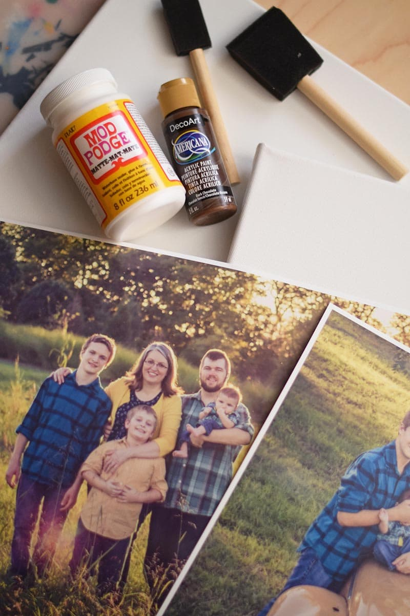 supplies for a photo transfer to canvas, including Mod Podge, acrylic paint, foam brushes, and family photos