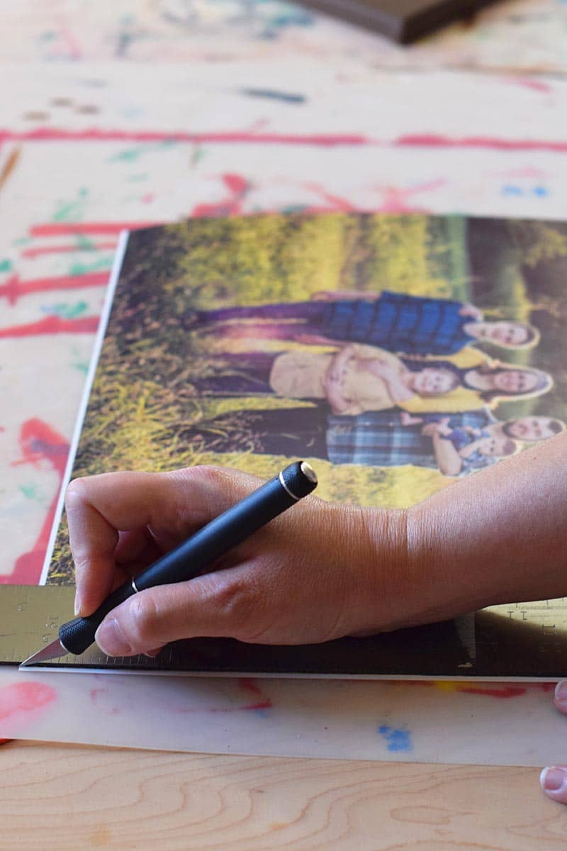 preparing to make a photo canvas by trimming the white edges off photos with a craft knife on a craft board