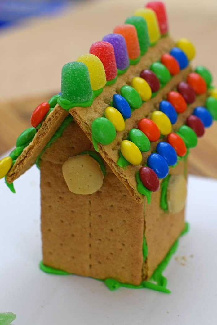 Make a fun and edible kids craft this St. Patrick's Day, a Graham Cracker Leprechaun House. Gather rainbow colored candies, Decorating Icing, and graham crackers, and you're all set!