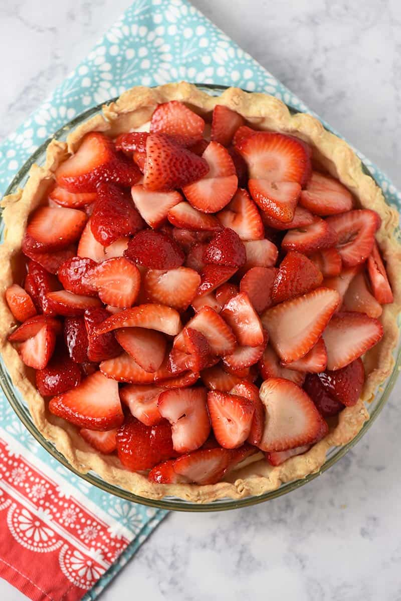 whole strawberry cream pie with fresh strawberries on a Pioneer Woman kitchen towel