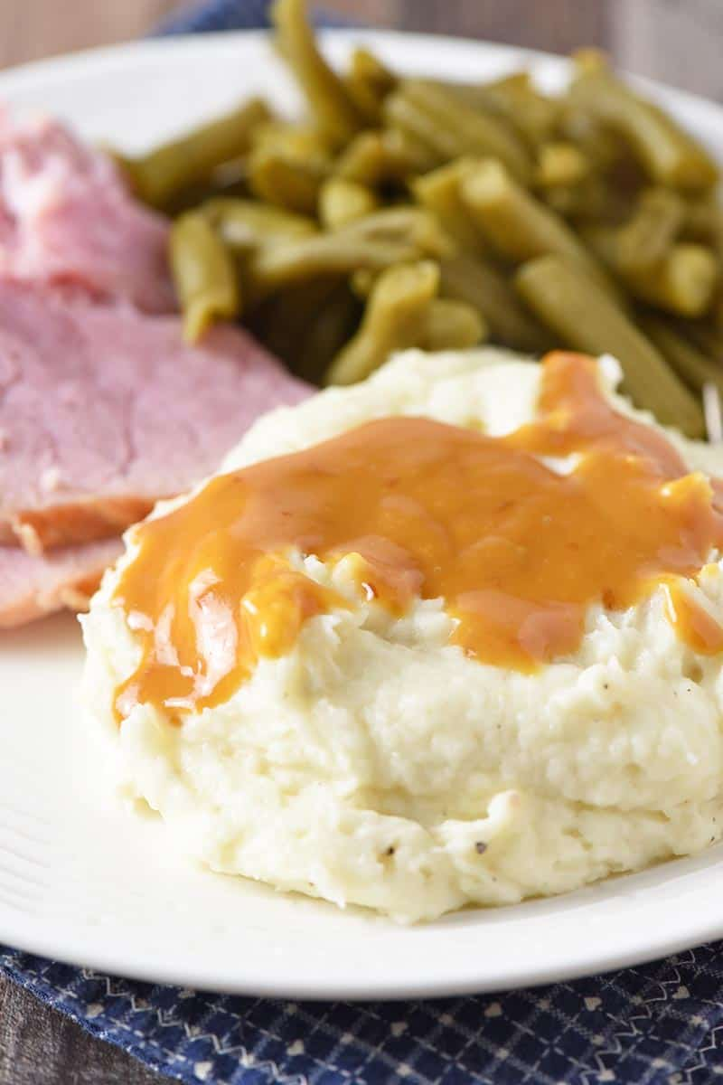 ham gravy on mashed potatoes served with ham and green beans on white plate