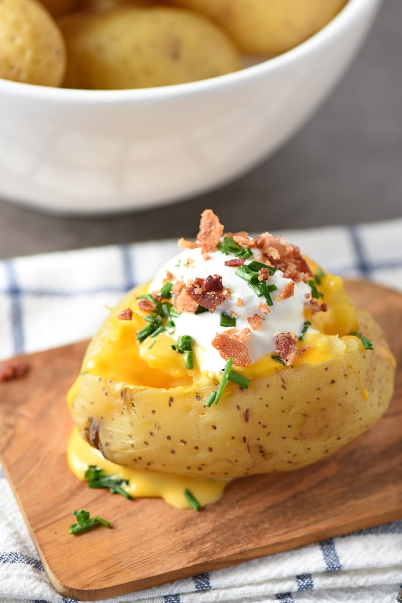 Instant Pot Baked Potatoes will be your new favorite dinner side, especially when you serve them up with all the fixings, like butter, sour cream, cheese sauce, crumbled bacon, chives, etc.