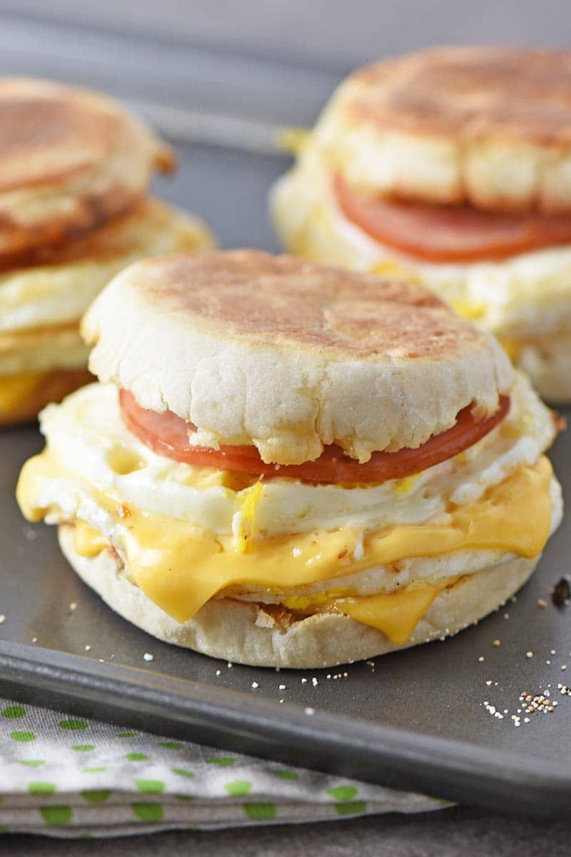Homemade Egg McMuffin with melted cheese, Canadian bacon, and eggs, on a baking sheet