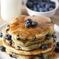 Blueberry Buttermilk Pancakes with maple syrup and fresh blueberries on a plate and milk to drink
