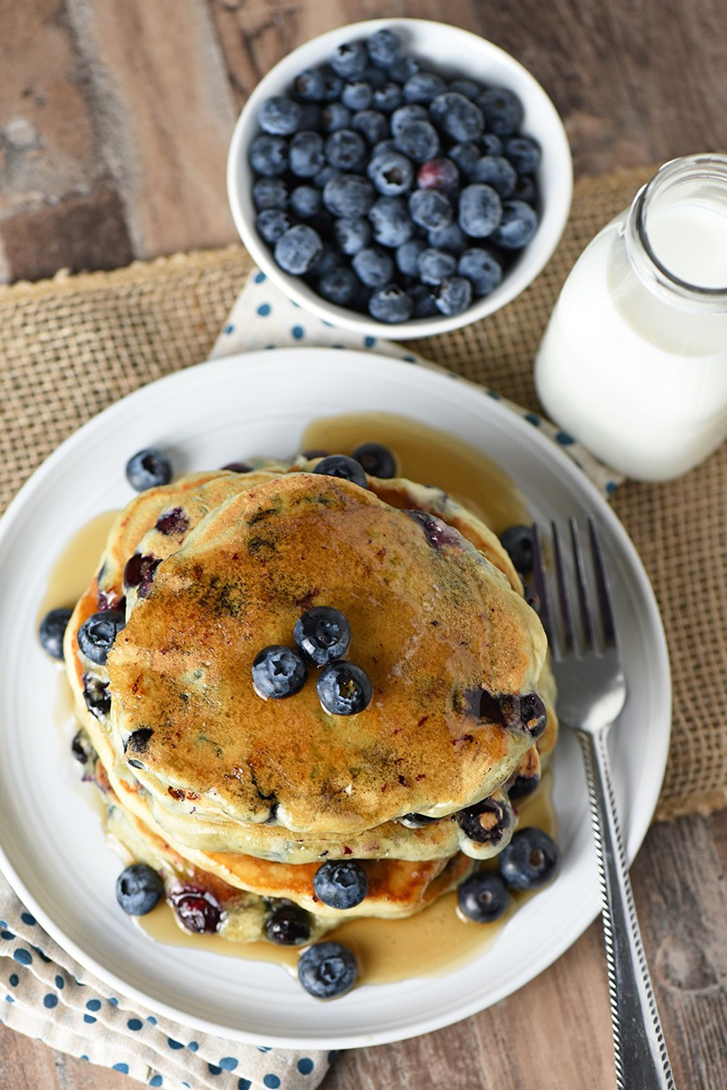 Blueberry Buttermilk Pancakes with maple syrup on a plate, fresh blueberries in a bowl, and milk in a glass bottle