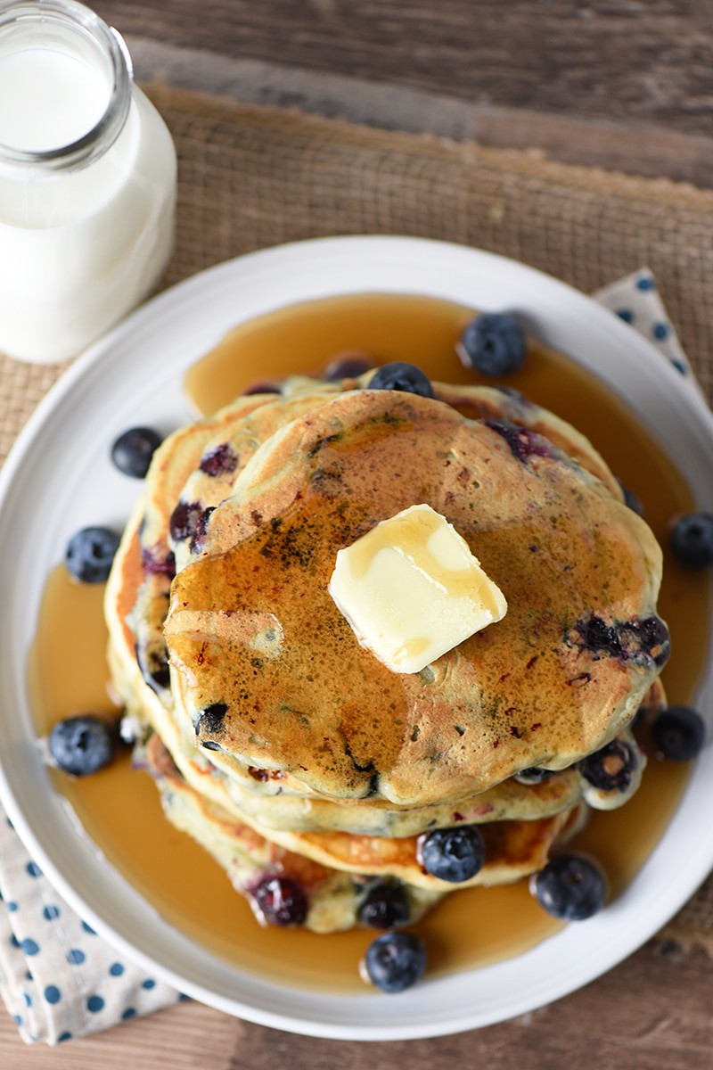 Blueberry Buttermilk Pancakes with butter and maple syrup on a plate, milk in a glass bottle on the side