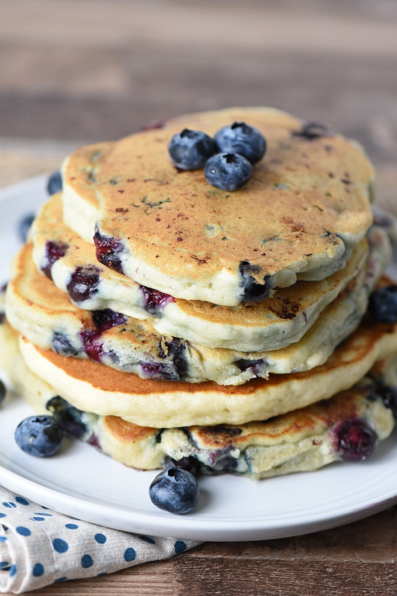 Stack of Blueberry Buttermilk Pancakes on a plate with fresh blueberries